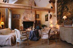 Sessel im Rokokostil und Sofa um Tisch mit drapiertem Tischtuch in rustikalem Wohnzimmer mit Holzkonstruktion