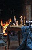 Sektgläser mit Flasche auf Tablett neben Schale und drapiertem Tischtuch auf schlichtem Holztisch vor Kaminfeuer