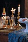 Gefüllte Sektgläser auf Tablett vor Messing-Kerzenständern mit brennenden Kerzen und Porzellanschale mit Konfekt auf Tischtuch
