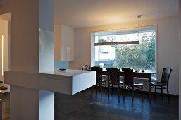 Blick auf Essbereich mit schlichtem Esstisch und Stühlen vor festverglastem Fensterelement