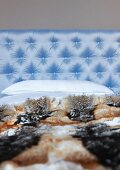 Animal skin blanket on bed with light blue satin headboard quilted with buttons