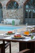 Nachmittagskuchen auf Terrassentisch im Innenhof einer mediterranen Wohnanlage mit Pool