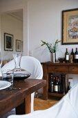 Gedeckter rustikaler Tisch mit Rotweinkaraffe und Wasserglas, Kommode mit Weinflaschen im Hintergrund