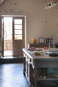 Traditioneller Küchenblock mit Spüle und Designer Armatur vor halboffener Terrassen- Flügeltür in schlichtem Landhaus-Esszimmer