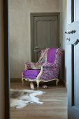 Blick durch offene Tür auf Lesesessel im Rokokostil mit Designer Stoffbezug und farbigem Punktmuster in Zimmertürecke