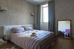 Doppelbett mit gepolstertem Kopfteil an Wand und Spiegel mit Goldrahmen auf Boden neben Fenster