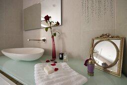 Badezimmerutensilien auf Designerwaschtisch mit Waschschüssel auf Glasplatte und Blumenvase neben Vintage Spiegel