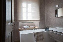 Designerbad - Blick durch offene Tür auf Badewanne vor Fenster mit heruntergezogenem Rollo und moderner Waschtischtrog an Wand