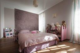 Doppelbett vor fliederfarbenem Raumteiler und halbhohes Regal mit Stofftieren in modernem Schlafzimmer