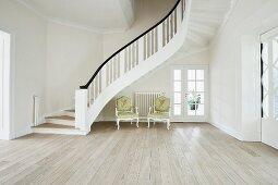 Modernes helles Wohnzimmer mit Holzboden, Treppenaufgang und Stilmöbeln