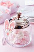 Glass jar with heart-shaped tag filled with miniature meringues