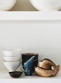 Verschiedenes Geschirr aus Porzellan, Keramik und Holz auf weißer Ablage arrangiert