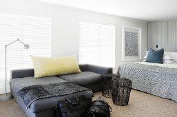 Dunkelgraue Sofakombination und Beistelltische aus Geflecht neben Doppelbett in modernem Schlafzimmer mit geschlossenen Jalousien