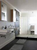 Zwei Waschbecken unter Spiegelschränken und abgetrennter, verglaster Duschbereich in modernem Ambiente