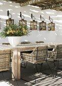 Lichteinfall durch Pergola auf Vintage Rattan Stühle mit Metallgestell an rustikalem Holztisch und Laternen an Hauswand aufgehängt