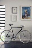 Racing bicycle on dark wooden floor below retro poster and miniature artworks