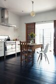 Eclectic dining set with retro elements in front of kitchen counter; glass wall with internal, sliding shutters