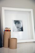 Coloured pencils in cardboard tube and black and white photographic portrait of woman in blurred background
