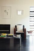 Minimalist artworks on wall above retro armchair and glass and metal coffee table