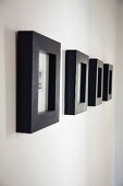 Row of small artworks in wide, black frames on white wall