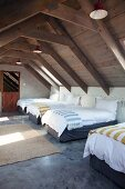 Several single beds with striped blankets in attic storey with exposed roof structure