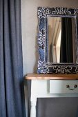 Mirror with ornate metal frame on rustic console table