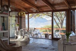 Offener Wohnraum mit Klassikerstühlen am Essplatz vor Panoramafenster und Blick über Terrasse auf Berglandschaft
