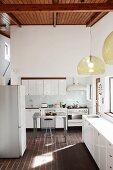 Hängeleuchten mit Glasschirmen in weisser Designerküche mit dunklem Terrakottaboden