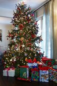 Many wrapped presents below magnificently decorated Christmas tree