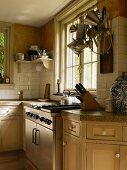 Shakerküche mit Steinarbeitsplatte und integriertem, modernem Herdblock in renoviertem Landhaus