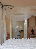 Bett mit weisser Decke und drapiertem Voile am Baldachingestänge, im Hintergrund Badezimmer