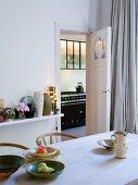 Holz Küchentisch und Blick durch offene Tür auf Vintage Küchenherd