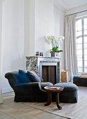 Beistelltisch im Ethnostil neben blauem Sessel mit passendem Fusshocker und Kissen vor Kamin in herrschaftlichem Wohnzimmer mit hohen Sprossenfenstern