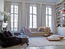 Sessel mit Fusshocker und Sofa vor raumhohen Sprossenfenster mit hellgrauen Vorhängen im Jugendstil Wohnzimmer