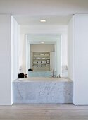 Bathtub with marble sides built into open niche and floor-to-ceiling mirror on opposite wall