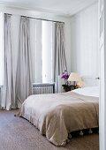 Blick durch offene Tür auf Doppelbett neben Fenster mit bodenlangen Vorhängen