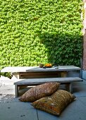 Ethnic cushions on floor in front of rustic wooden bench and table in sunny courtyard with creeper-covered wall