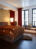 Grand bedroom with fur blanket on impressive double bed; shiny, gold wall behind upholstered headboard