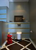 Wall-mounted toilet in elegant bathroom with pastel blue and gold mosaic tiles; gold ornament on red side table in foreground