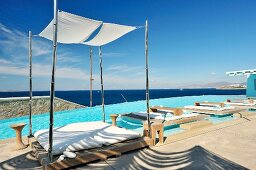 Loungers on floating wooden decks in swimming pool with view of ocean