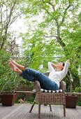 Woman sitting on garden chair with legs stretched out on terrace