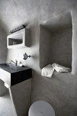 Stone washstand and niche in pale grey, limewashed wall in minimalist bathroom