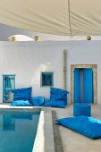 North-African-style courtyard with blue floor cushions and pouffes around pool