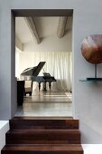 View from grey-painted foyer through open doorway with wooden steps into modernised interior with grand piano