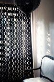 Dark wooden chair with white upholstery next to curtain with white wavy pattern on dark fabric