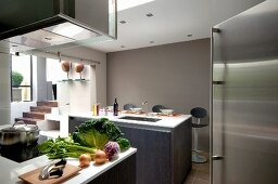 Vegetables on counter below extractor hood in designer kitchen decorated in various shades of grey