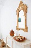 Marokkanischer Spiegel über Konsolentisch mit Tongefäss und Muschelsammlung