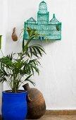 Blau lackierter Palmentopf und Tongefäss unter altem orientalischem Vogelkäfig in Zimmerecke