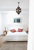 Einfaches Bett mit holzverschaltem Kopfteil und bunten Kissen unter orientalischer Hängelampe