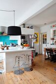 Pendant lamps with black lampshades above modern island counter with designer barstools on wooden floor
